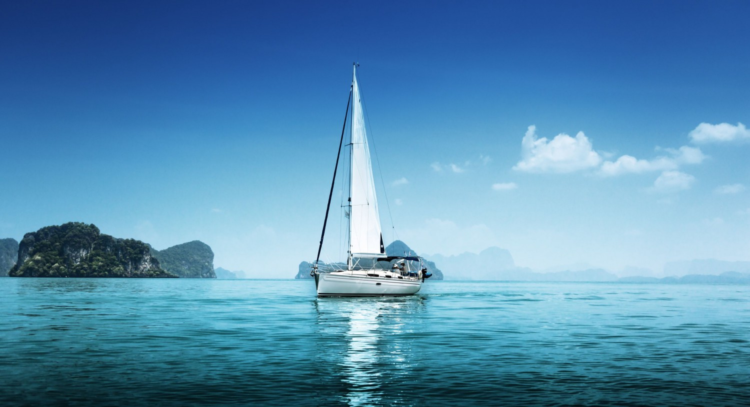 Lean sailboat in blue, protected waters with just the mainsail up