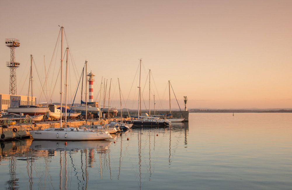 Sailboats docked at sea marina with lighthouse in background at dusk