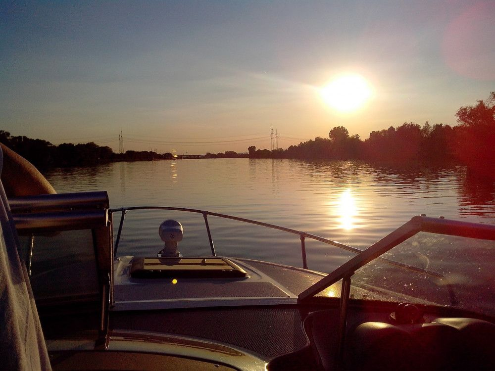 Sunset in calm waters from a boat with small outboard motor