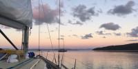 Sailboat motoring at dawn