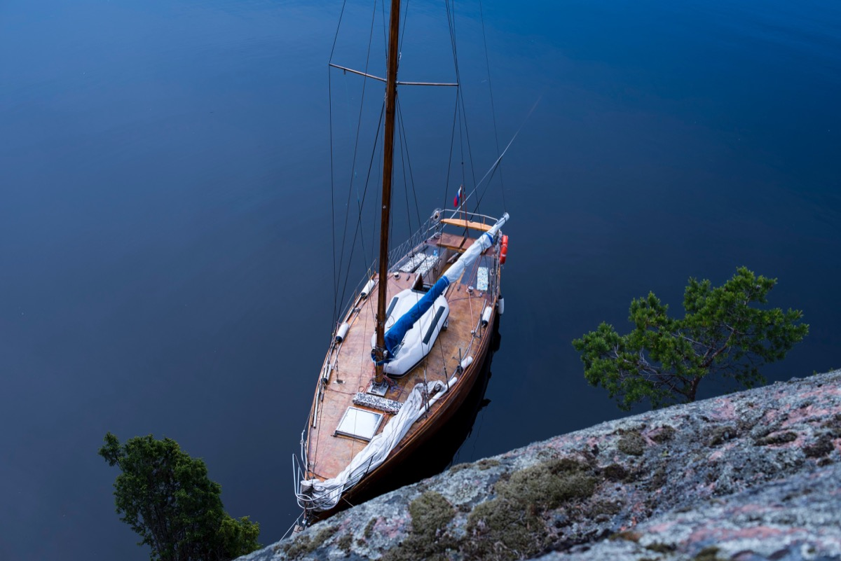 Small sailboat with wooden deck anchored at shore