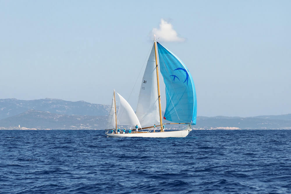 White yawl with white sails and bright blue spinnaker on Medditerrenean