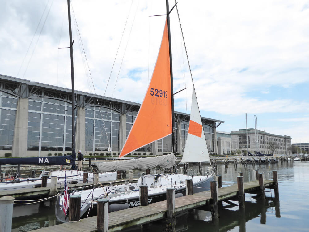 US naval acadamy sloop in marina with bright orange storm trysail and stormjob