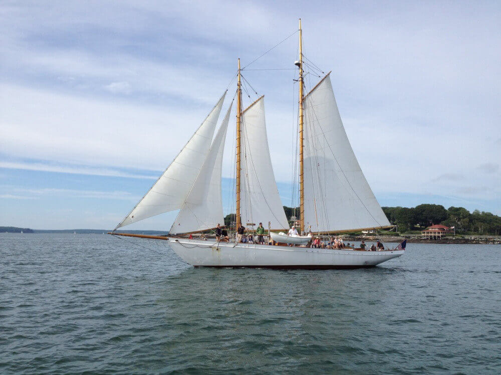 White schooner with white sails and light wooden masts