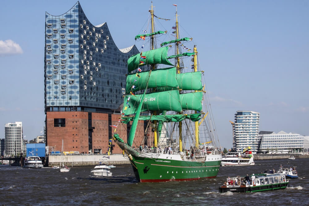 Green tall ship with green square rigged sails against urban background