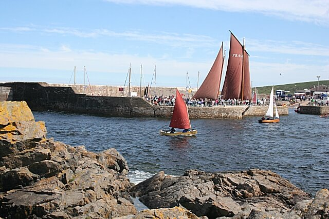 Lugger sails behind berth with rocks and small sloops in the foreground