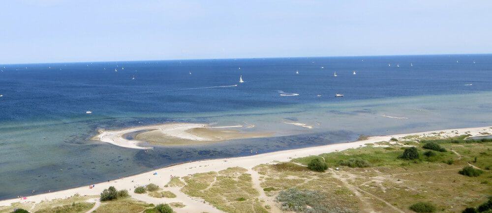 Birdseye view of beach and coastline with lots of small sailboats
