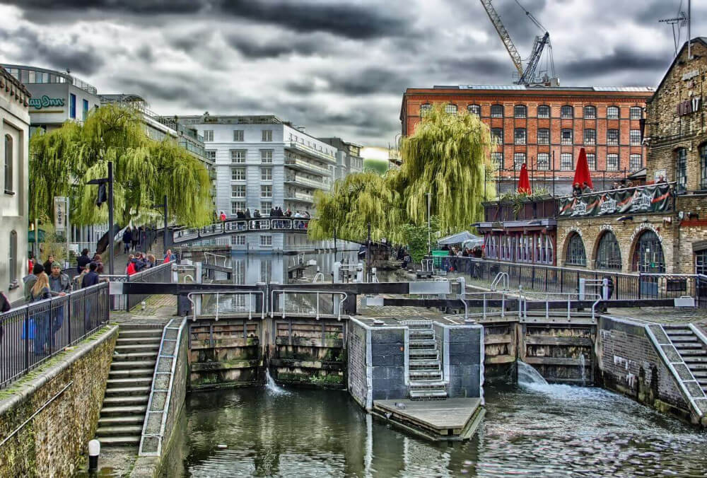 Canal lock in middle of London, UK, with grey sky and orange building