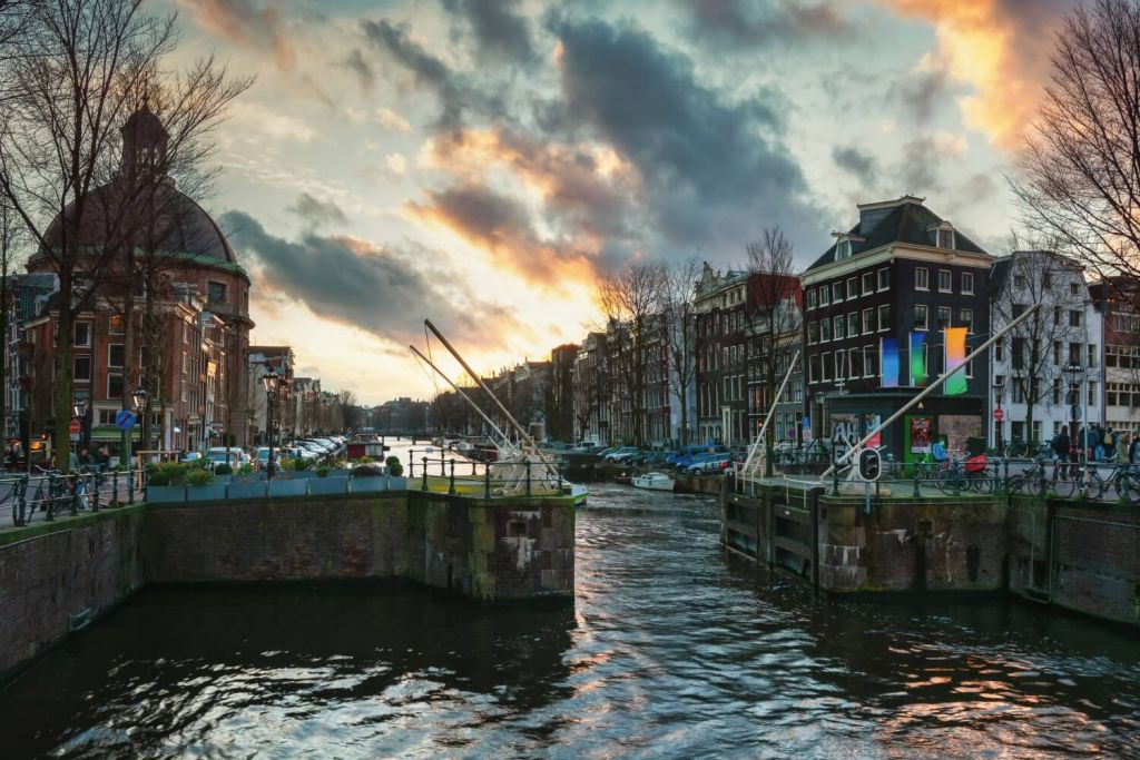 Canal lock in city of Amsterdam with old buildings