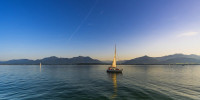 Smooth water sailboat panorama with dusk setting in