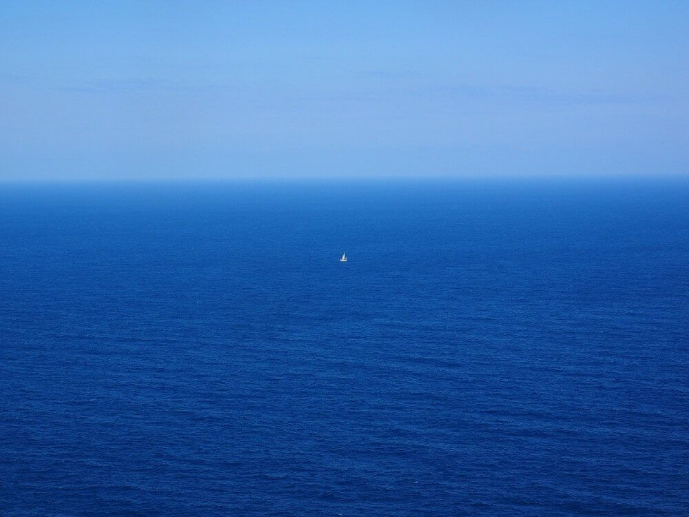 Small sailboat in middle of huge blue sea