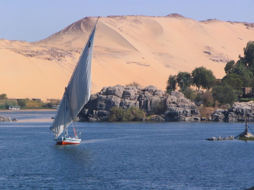Sailboat in coastal waters with desert hill in the background