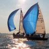 Italian sailboats with blue sails competing in sunny weather