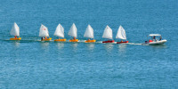 Sail instructor tows seven dinghies with a powerboat