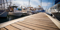Wooden boardwalk in marina with boats tied up on either side