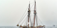 Two-masted, classical sailboat sailing under power