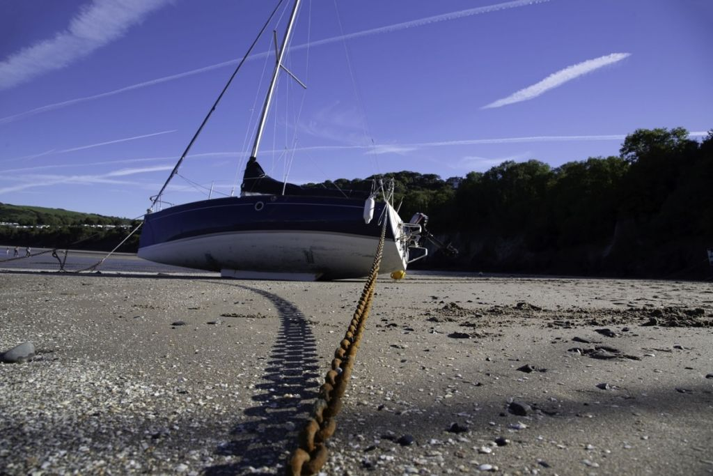 Sailboat with anchor chain in sand