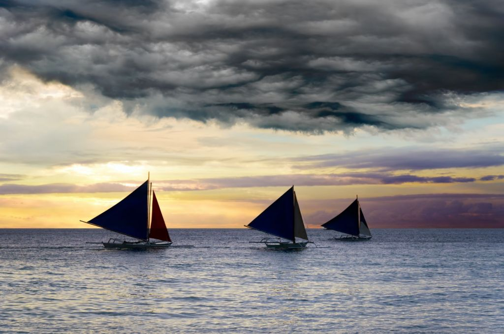 3 Sailboats with dark sails under dark clouds at sunset