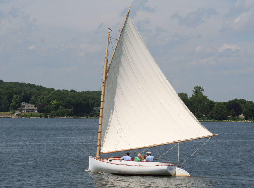 White cat boat with single gaff-rigged sail