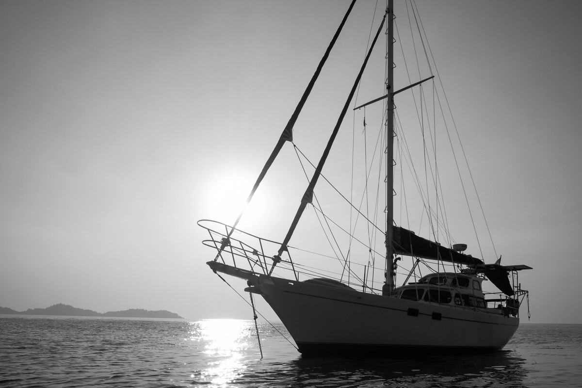 Cutter motorsailor against sun in black and white