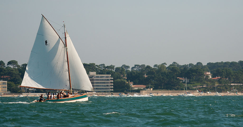 Gaff Rigged Sloop in white in front of coastline with flat