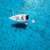 A sailboat at anchor from above in clear blue waters