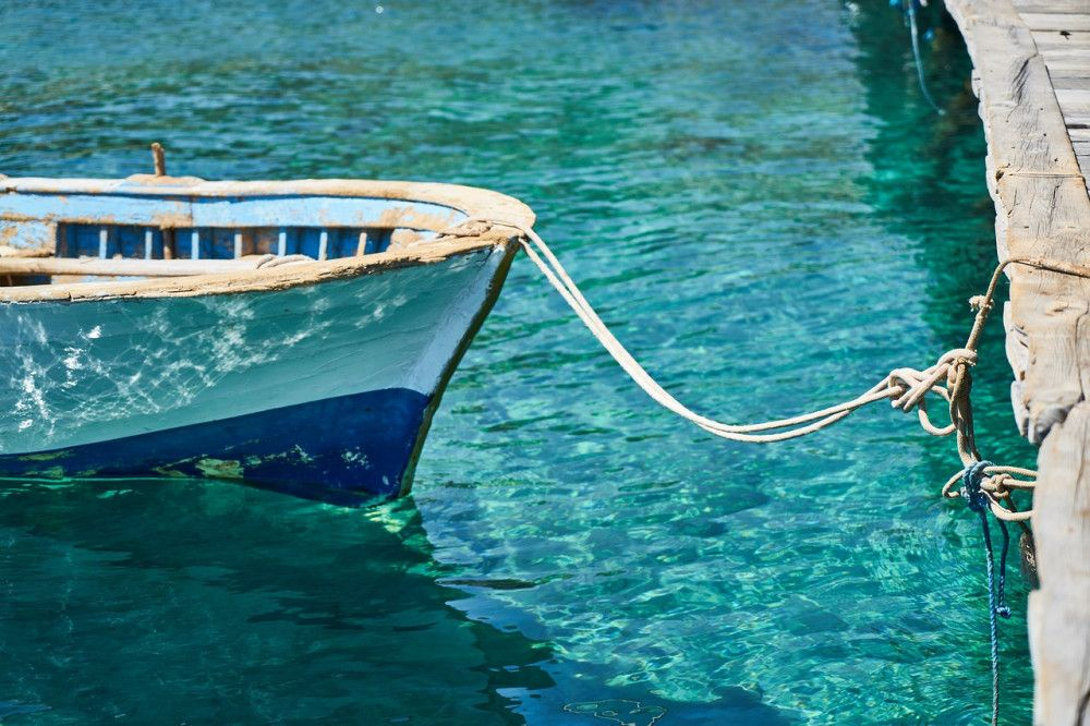 Small boat in blue water of marina