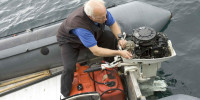 Old man works on boat engine