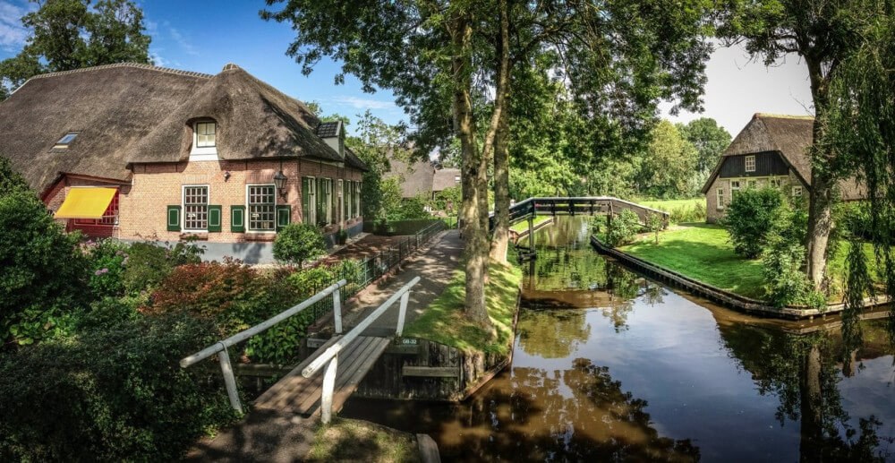 Beautiful farm near small canal with small wooden bridges, in Giethoorn, Holland.