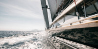 Bow shot of black wooden cruising sailboat