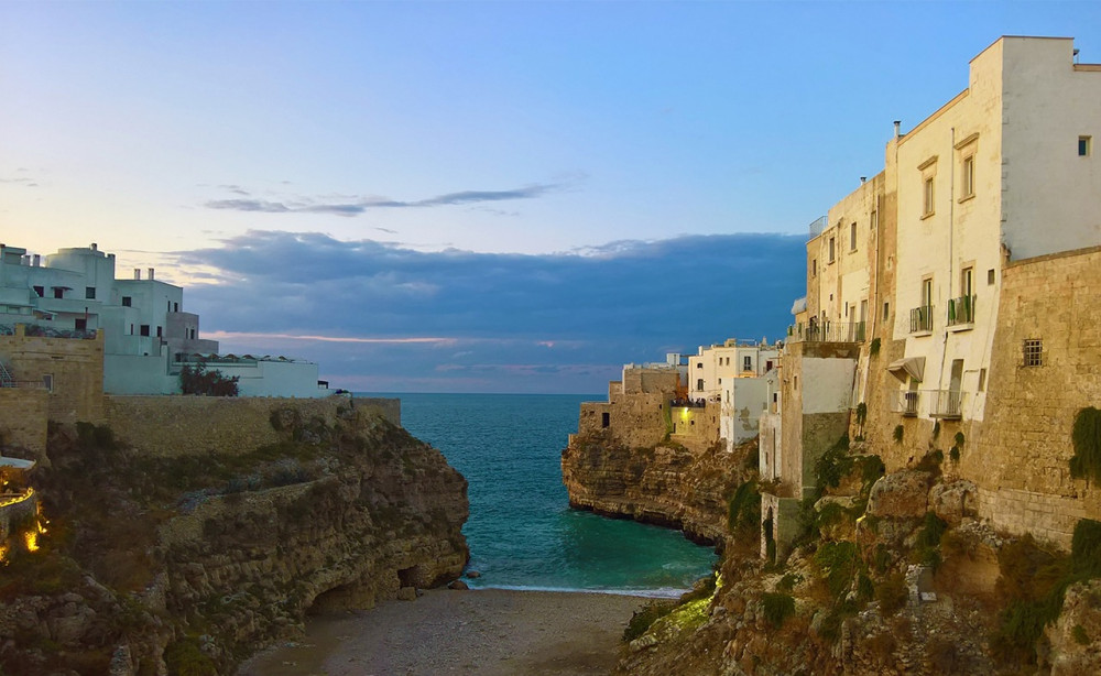 Small bay with tall white buildings on cliffs at sunset